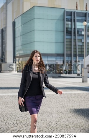 Young business woman in hurry - walking street with notebook bag - stock photo