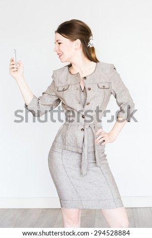 Young business woman in office dress is looking her smart-phone - stock photo
