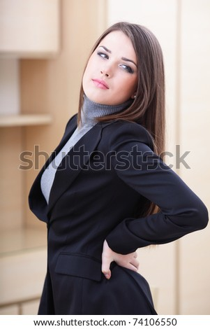 Young business woman in office holding her lower back in pain