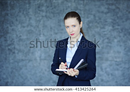 Young business woman in suit writing in a diary, textured background, look at camera, copy space. - stock photo