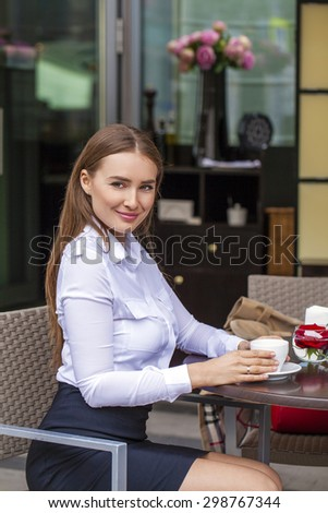 Young Business woman in white shirt drinking a cup of coffee in a summer cafe