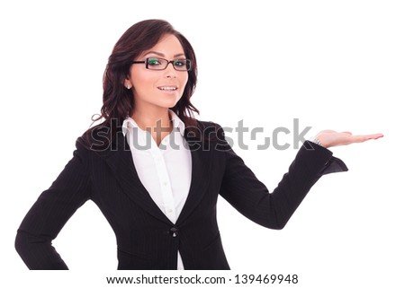 young business woman is holding something imaginary in her palm, while smiling to the camera. on white background - stock photo