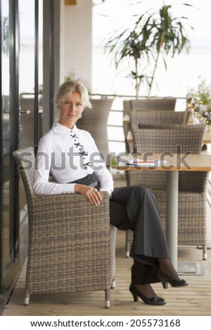 young business woman is resting in wicker chair