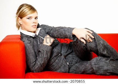 Young business woman is resting on the red couch