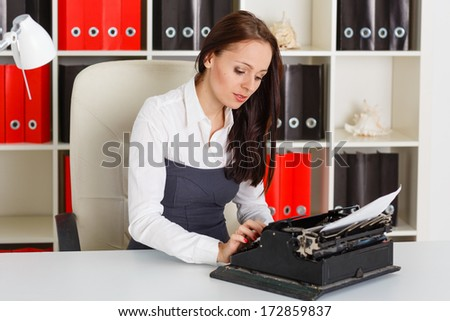 Young business woman is typing document with an old typewriter in the office.