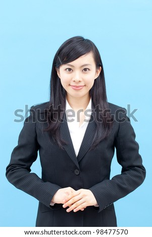 Young business woman isolated on blue background - stock photo