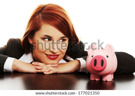 Young business woman looking on pink piggy bank, isolated on white background  - stock photo