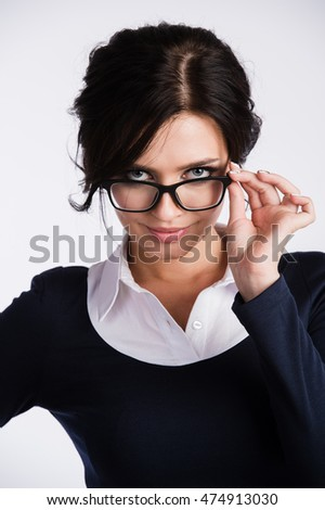 Young business woman looking skeptically over her spectacles, on white background