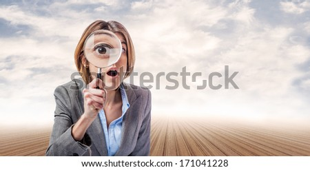 young business woman looking through a magnifying glass at an abstract place - stock photo