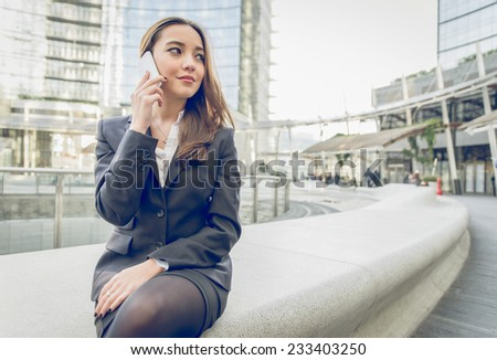 young business woman making a phone call after work - stock photo