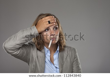 Young business woman measuring her body temperature using a thermometer - stock photo