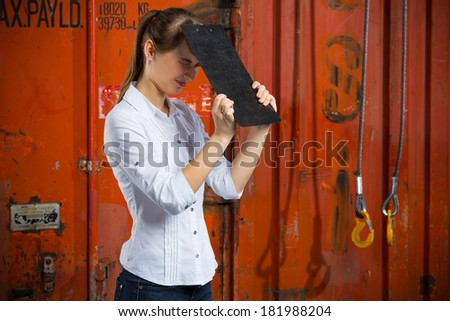 Young business woman on a containers background is hitting herself with a clipboard in despair and anxiety because of a logistics management problem - stock photo