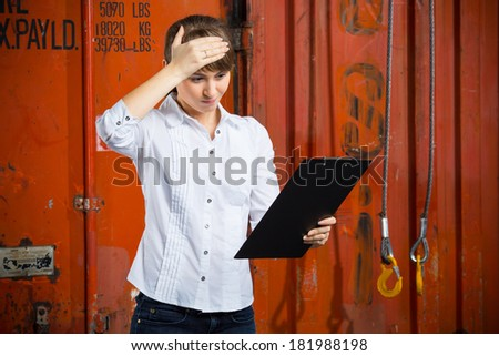 Young business woman on a containers background is struggling trying to solve a logistics management problem - stock photo