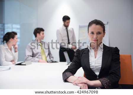 young business woman on meeting usineg laptop computer, blured group of people in background at  modern bright startup office interior taking notes on white flip board and brainstorming about plans  - stock photo
