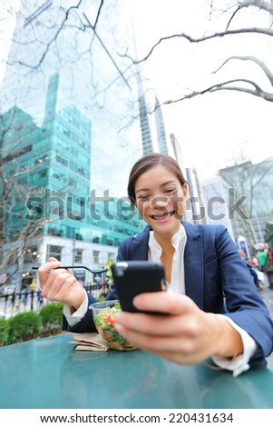 Young business woman on smartphone eating salad on lunch break in City Park living healthy lifestyle working on smart phone. Happy multiracial businesswoman, Bryant Park, manhattan, New York City, USA - stock photo