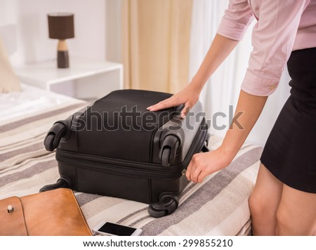Young business woman packing her suitcase on bed at the hotel room. Close-up. - stock photo