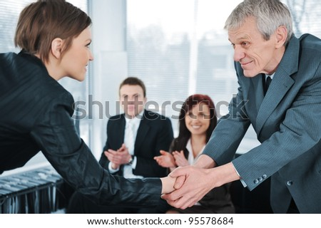 Young business woman passed on a job interview shaking hands with boss - stock photo