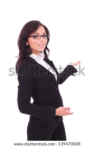 young business woman presenting something in the back while looking at the camera with a smile on her face. on white background