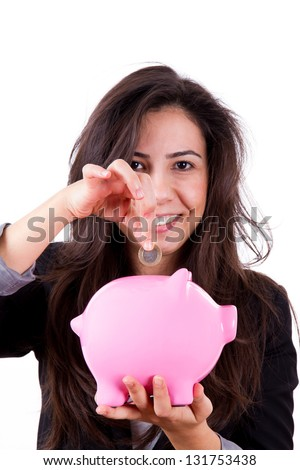 Young business woman puts her financial item coin into pink piggy bank, isolated on white background.