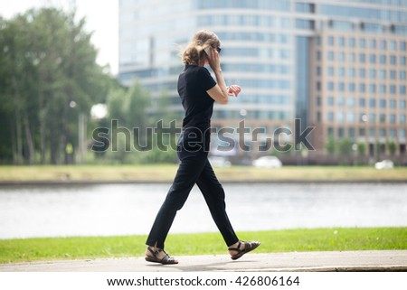 Young business woman running late, walking at fast speed, looking at wristwatch, talking on smartphone on the city street in front of blue glass modern office building, full length - stock photo