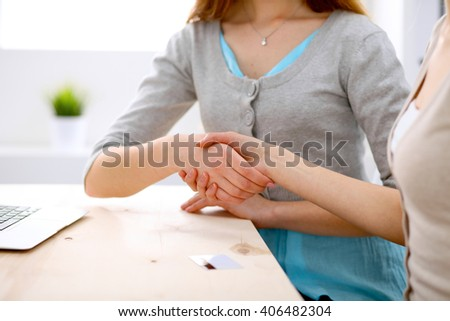 Young business woman shaking hands  sitting at the desk  - stock photo