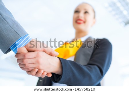 young business woman shaking hands with a client, the agreement between the partners - stock photo