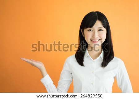 young business woman showing copy space against orange background - stock photo