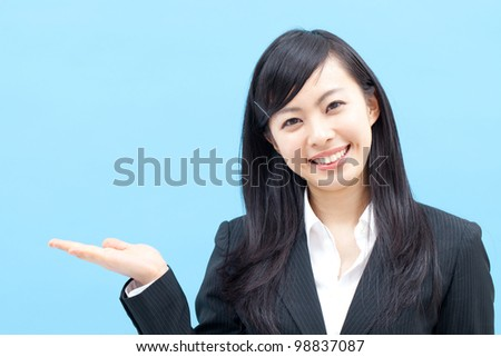young business woman showing something, isolated on blue background