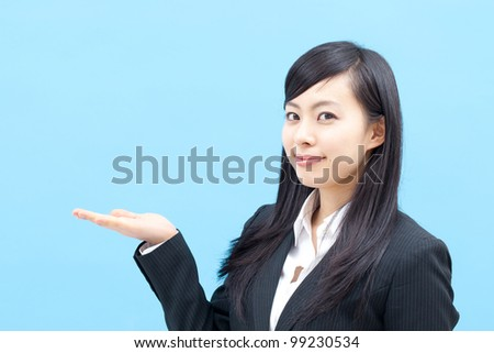 young business woman showing something, isolated on blue background - stock photo