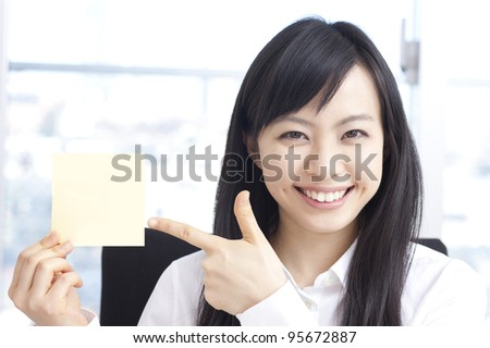 Young business woman showing sticky note. - stock photo