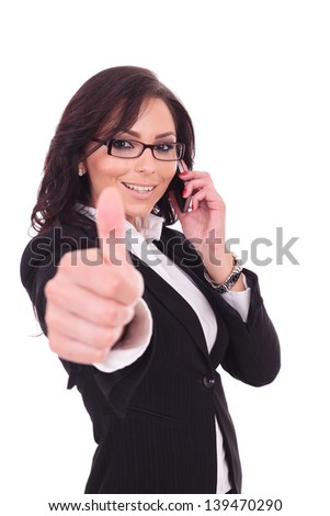 young business woman showing thumb up sign while speaking on the phone. on white background
