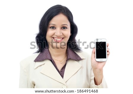 Young business woman showing with black display of mobile phone against white - stock photo