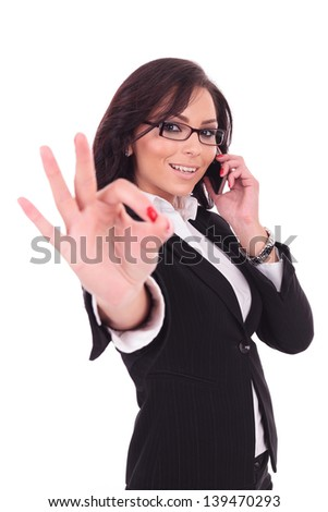 young business woman shows the ok sign while on the phone, smiling at the camera. on white background