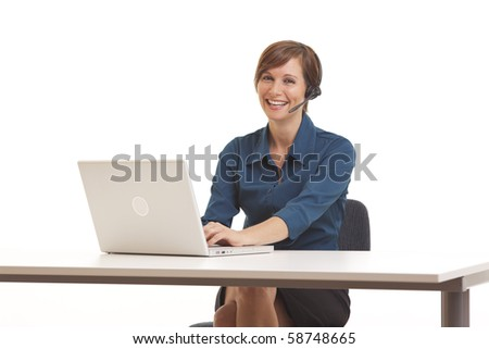 Young business woman sitting at desk with laptop and headset - stock photo