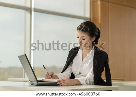 Young business woman sitting at her desk in an office, working on a laptop computer and planning a new project