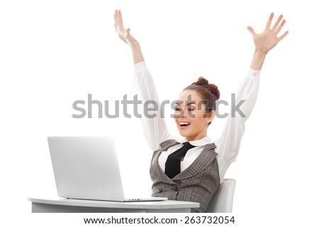 Young business woman sitting at table with a laptop , arms raised in victory. - stock photo