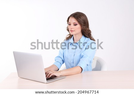 Young business woman sitting at table with notebook in room