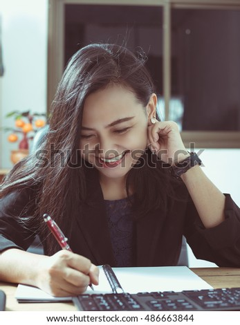 young business woman sitting at the desk on office background
