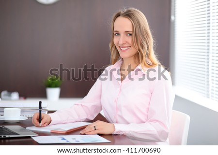 Young business woman sitting at the table in the office - stock photo