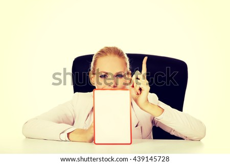 Young business woman sitting behind the desk and holding a board with ban - stock photo