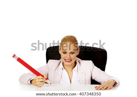 Young business woman sitting behind the desk and holding big pen - stock photo