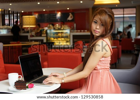 Young business woman sitting in cafe with her laptop.