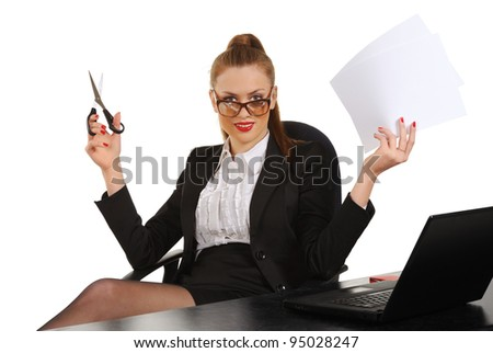 Young business woman sitting in office chair with scissors - stock photo