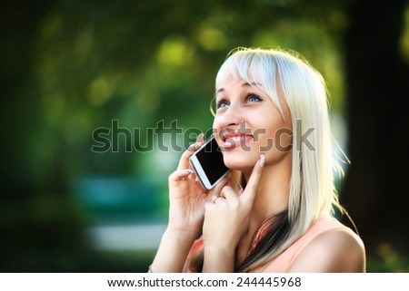 Young business woman sitting on a park bench and talking on a cell phone outdoors - stock photo