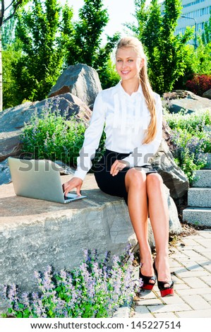 Young business woman sitting on a rock and using a laptop outdoors - stock photo