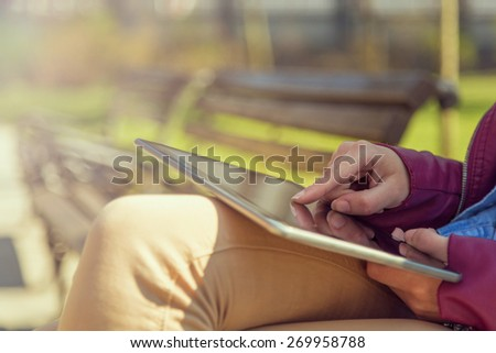 Young business woman sitting on a wooden bench in a park and making a business report - stock photo