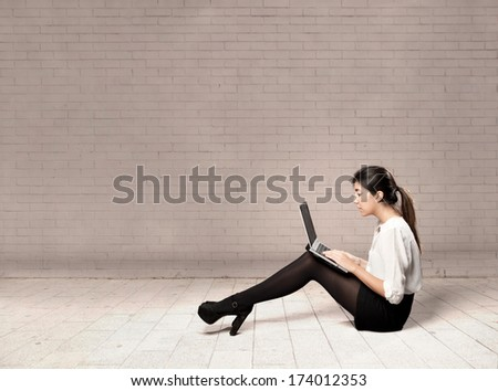 young business woman sitting on floor using a laptop