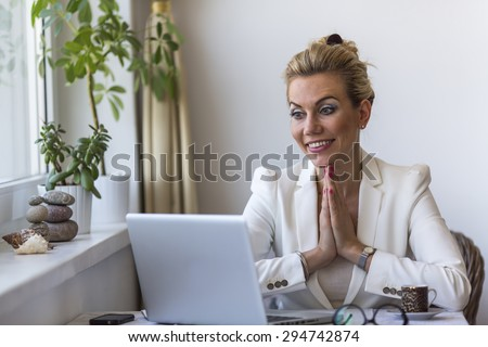 Young business woman sitting with hands clasped in front of the computer. - stock photo