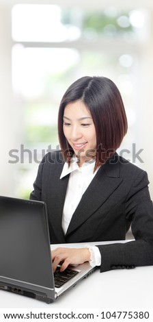 Young Business woman smile using notebook pc and sit at company office with white table, window outside are green background, model is a asian beauty - stock photo