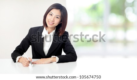 Young Business woman smile working and sit at company office with white table, window outside are green background, model is a asian beauty - stock photo